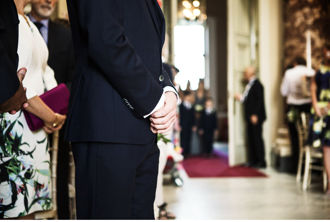 Groom's hands closeup as Bridal party arrives