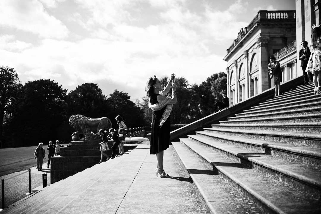 A wedding guest taking pictures at Stowe House