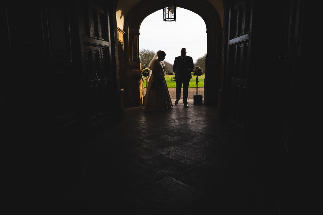 Bride and Groom walking in the front door at Hengrave Hall