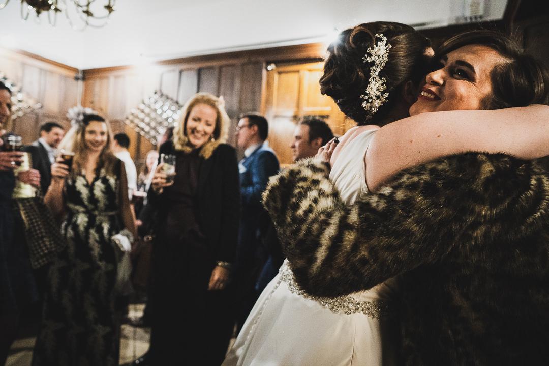 Bride hugs a friend at wedding