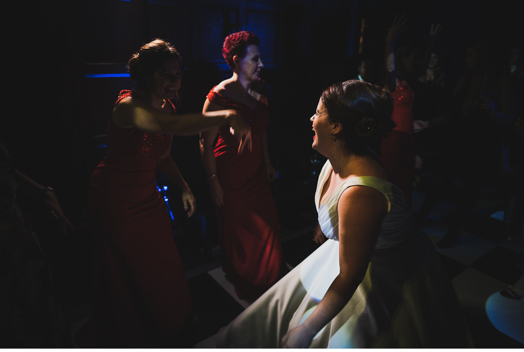 Bride laughing with friends on the dance floor