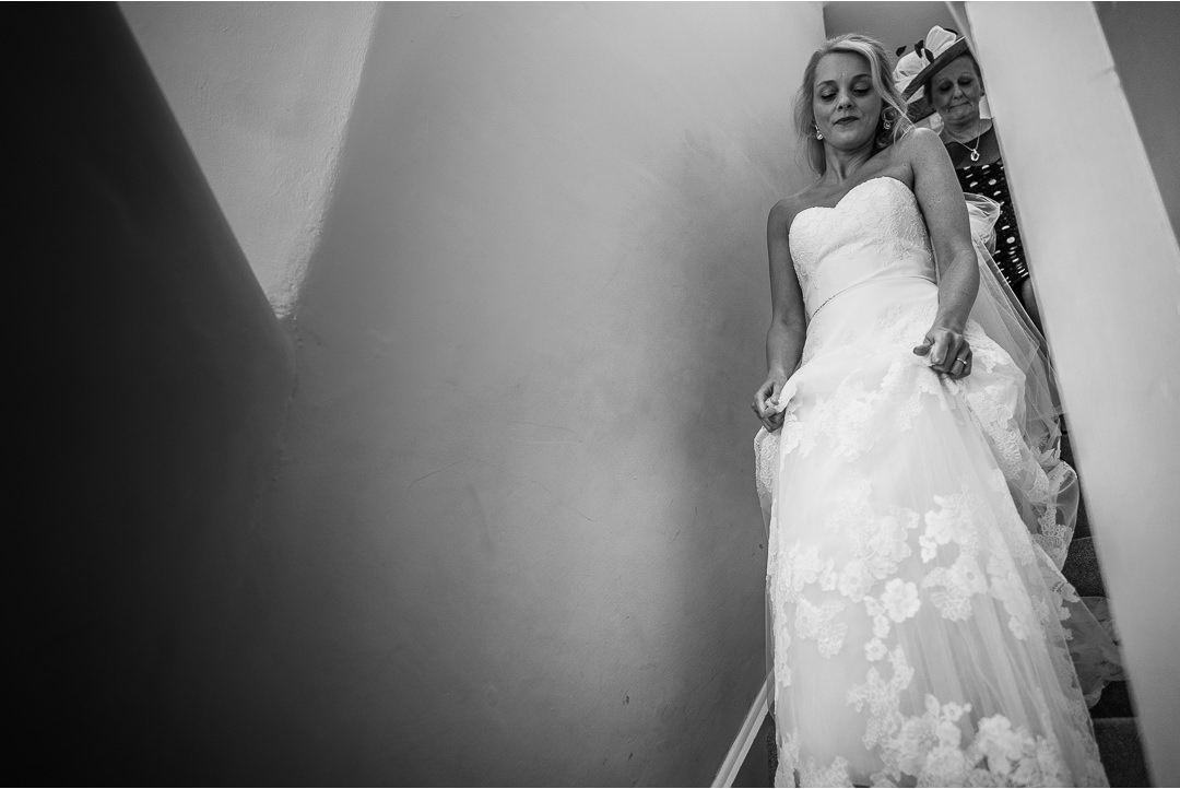 Bride walking down the stairs in the Gatehouse at Farnham Castle