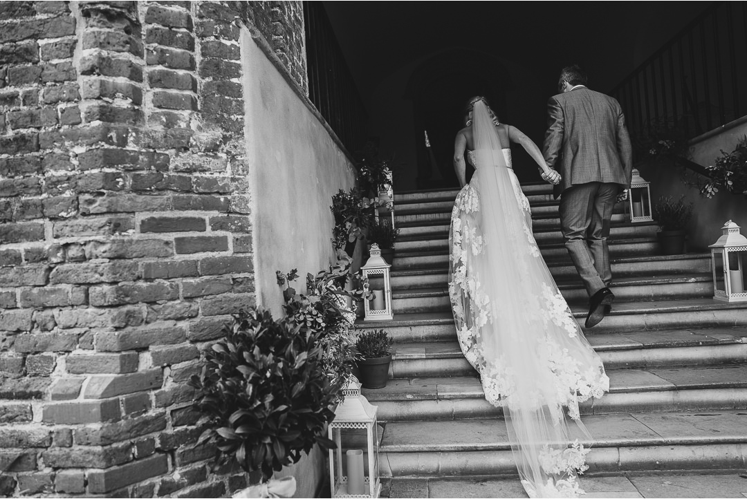 Bride and Groom walking up the steps at Farnham Castle