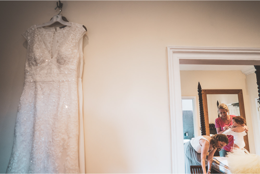 Wedding dress hanging up as Bride gets ready