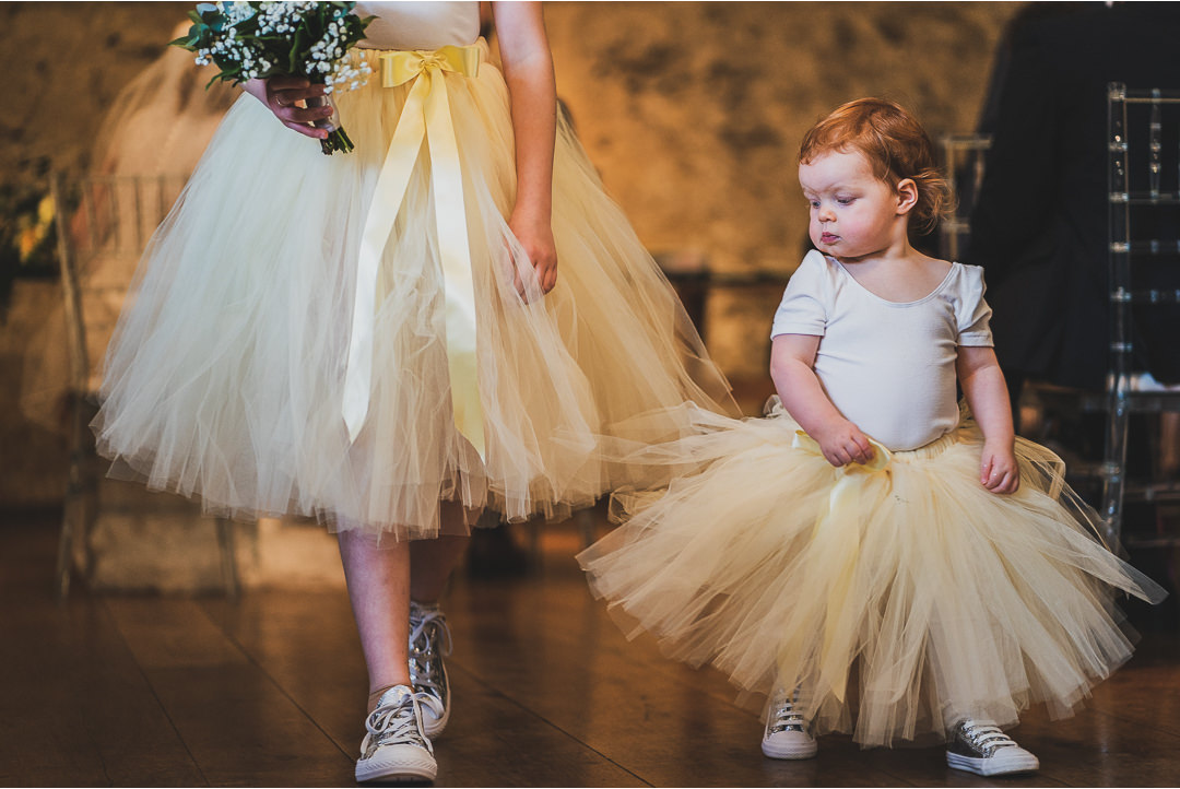 The flowergirl looking at a Bridesmaid's shoes
